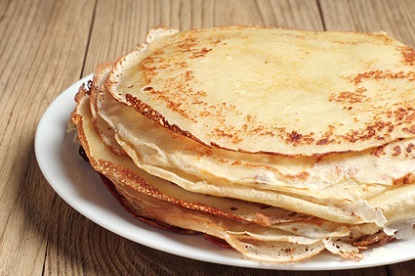 Stack of pancakes on wooden table closeup